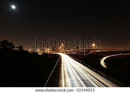 Houston skyline with highways under night sky with moon and stars - stock photo