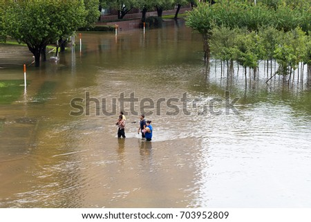 Houston, Texas - August 27, 2017: Houston residents walk across the flooded street in Houston, Texas, USA. Heavy rains from hurricane Harvey caused many flooded areas in Houston.