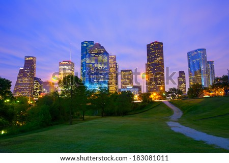 Houston Texas modern skyline at sunset twilight from park lawn - stock photo
