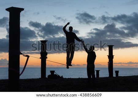 HOVE, ENGLAND - JANUARY 19, 2014 - Silhouettes of people practicing to walk a slack line. One person holding the other's hand to help with their balance.
