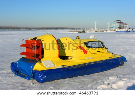 Hovercraft on the bank of a frozen river against a blue sky