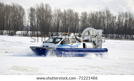 Hovercraft rides on the frozen river, picking up snow dust. Winter - stock photo