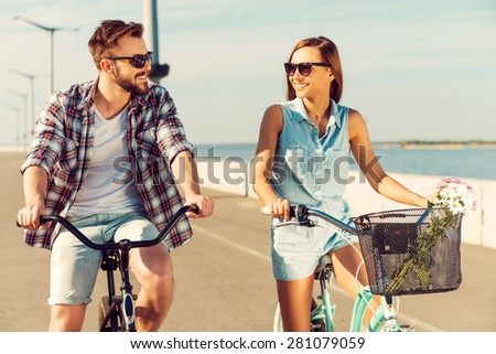 How about race? Cheerful young couple looking at each other with smiles while riding on bicycles along the road - stock photo