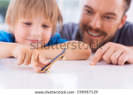 How are you doing like this? Cheerful father looking at his sun playing with fingerboard and smiling  - stock photo