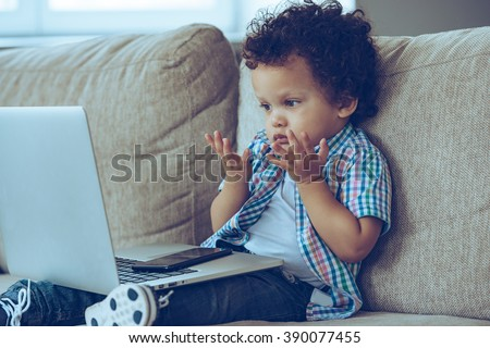 How does this thing turns on? Little African baby boy looking confused while sitting on the couch at home with laptop on his knees - stock photo