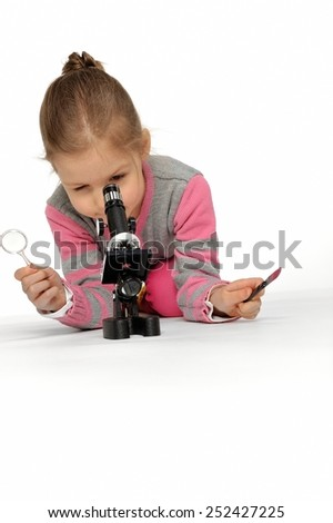 How interesting to see small objects. When I grow up, I will be a scientist. Little girl looking through a microscope.