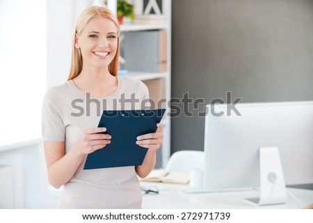 How may I help you? Beautiful young woman holding clipboard and smiling while standing near her working place in office - stock photo