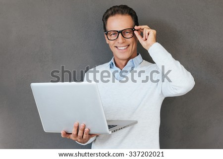 How may I help you? Confident mature man holding laptop and smiling while standing against grey background  - stock photo