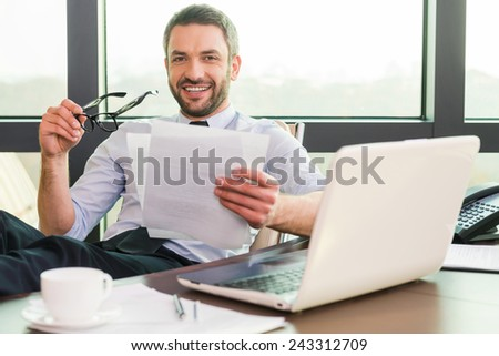 How may I help you? Handsome mature man in shirt and tie adjusting his eyeglasses and smiling while sitting at his working place - stock photo