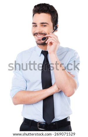 How may I help you? Handsome young male operator adjusting his headset and smiling while standing against white background - stock photo