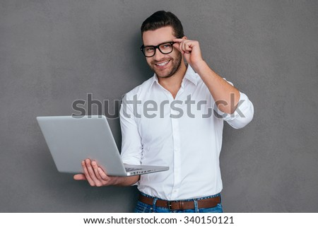 How may I help you? Handsome young man holding laptop and smiling while standing against grey background - stock photo