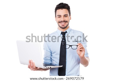 How may I help you? Handsome young man in shirt and tie holding laptop and smiling while standing against white background - stock photo