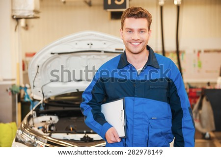 How may I help you? Handsome young man in uniform holding clipboard and smiling while standing in workshop with car in the background - stock photo