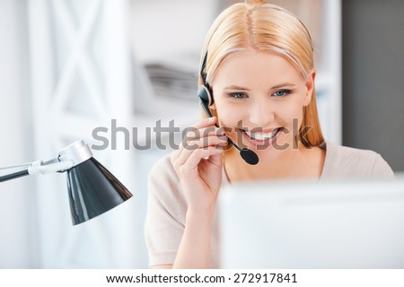 How may I help you? Happy young woman working at the computer and adjusting her headset while sitting at her working place - stock photo