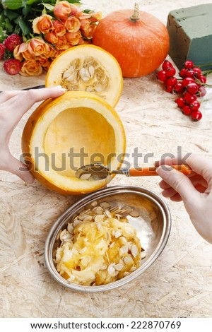 How to make a Thanksgiving centerpiece - step by step: removing the loose pulp and seeds from the pumpkin. - stock photo