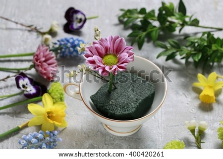 How to make floral arrangement inside vintage ceramic cup. Cup of flowers, beautiful decoration. - stock photo