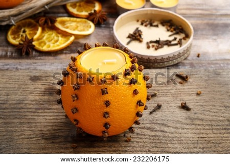 How to make orange pomander ball with candle - step by step, tutorial - stock photo