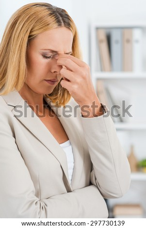How will I get through this day? Depressed mature businesswoman touching her nose and keeping eyes closed  - stock photo