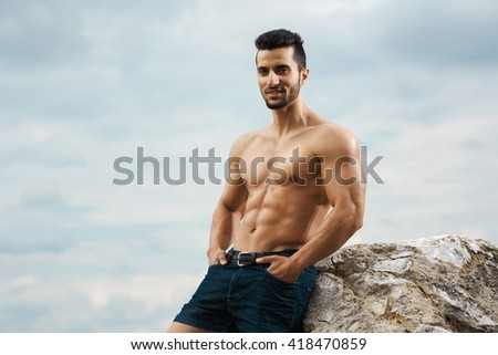 How you doing. Waist up shot of a muscular athlete posing showing off his fit and toned athletic torso looking to the camera. - stock photo