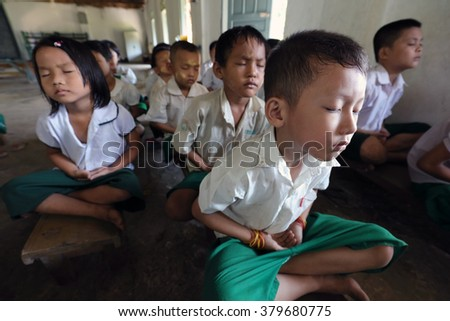 HPA AN - MYANMAR - NOVEMBER 13, 2015: Unidentified meditating students in a Buddhist monastery on November 13, 2015 in Hpa An, Myanmar. Burma is one of the most devout Buddhist countries in the world - stock photo