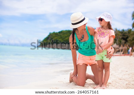 Hppy family of mom and girl during summer beach vacation - stock photo