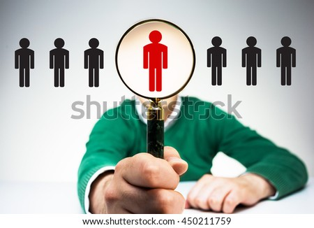 HR manager with magnifier choosing the right employee from variety of condidates. Human resources management and recruitment concept - stock photo
