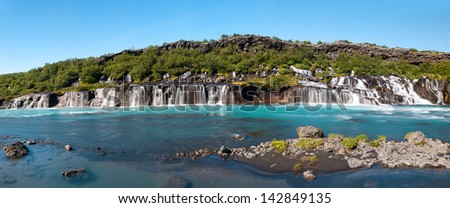 Hraunfossar is a very beautiful Icelandic waterfall in the west of the island. It comes from the lava field and pours into the Hvita river with a incredibly blue water. Panorama - stock photo