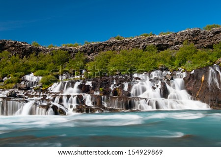 Hraunfossar is a very beautiful Icelandic waterfall in the west of the island. It comes from the lava field and pours into the Hvita river with a incredibly blue water. Long exposure. - stock photo