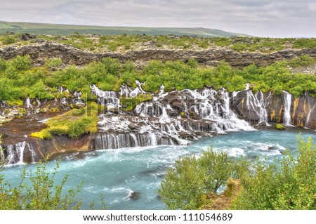 Hraunfossar Waterfall, Iceland - This waterfalls is formed by rivulets streaming over a distance of about 900 meters out of the Hallmundarhraun, a lava field which flowed from a volcanic eruption. - stock photo