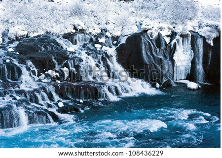 Hraunfossar waterfall in winter. Icelandic waterfall flowing through lava field.