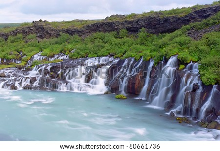 Hraunfossar (Western Iceland) is a series of waterfalls formed by rivulets streaming over a distance of about 900 meters out of the Hallmundarhraun,Iceland - stock photo