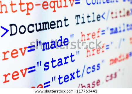 HTML source code of web page with document title, metadata description and links monitor screenshot diagonal view, small depth of sharpness - stock photo
