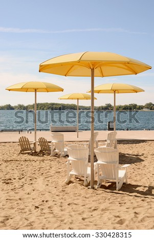 HTO is a public urban beach in Toronto. The park's standout feature is a sandpit that holds Muskoka chairs and enormous fixed yellow metal umbrellas./HTO Park Beach - stock photo