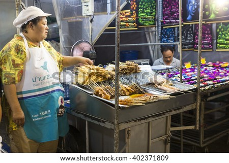 HUA HIN, THAILAND - MARCH 09, 2016: Staff offering meat and vegetables meal at stall with street food in local night market, Prachuap Khiri Khan Province