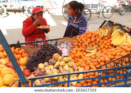 HUARAZ, PERU - AUG 8 -  Peruvian Indian farmer sells fresh fruit in wagon, on Aug 8, 2008, in Huaraz,  Peru - stock photo