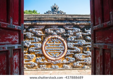 Hue Citadel Complex. The old gate and a wall decorated with traditional Vietnamese mosaic made of porcelain. Vietnam