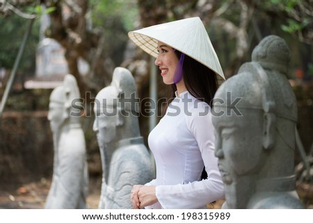 HUE, VIETNAM, MAY 3: Vietnamese girl with Ao Dai in Tu Duc royal tomb on May 3, 2014 in Hue, Vietnam. Ao dai is famous traditional costume for woman in VIetnam.