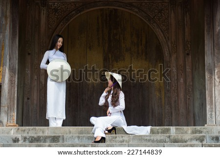 HUE, VIETNAM, MAY 3: Vietnamese girls with Ao Dai in Tu Duc royal tomb on May 3, 2014 in Hue, Vietnam. Ao dai is famous traditional costume for woman in VIetnam.