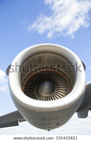 Huge aircraft jet engine from low point of view. Blue sky in the background. Big turbine blades are numbered.