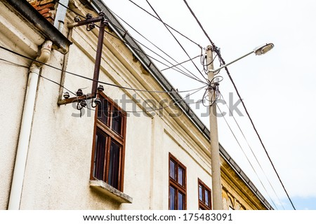 Huge amount of wires hanging freely everywhere. This photo shows them in front of a typical housing complex. - stock photo