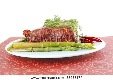 huge beef chunk on blue dish with asparagus