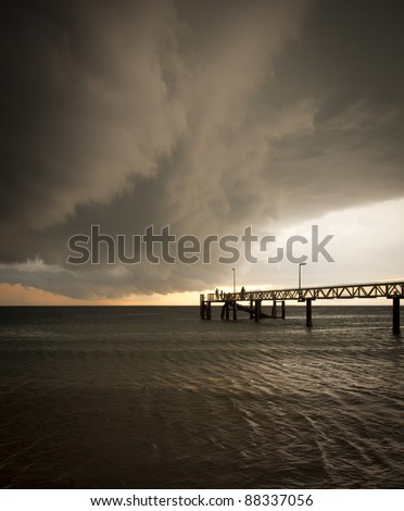 Huge black storm clouds gather as silhouetted people fish off a pier