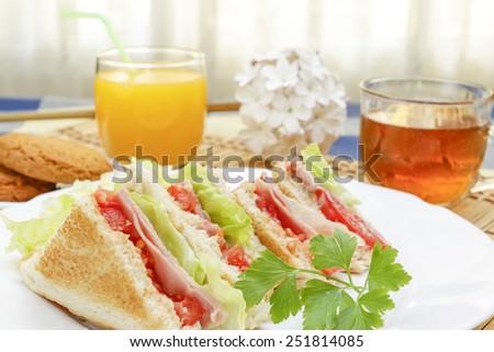 Huge breakfast with sandwich, orange juice, sweet and tea - stock photo