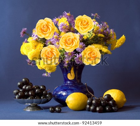 Huge bunch of autumn flowers and yellow roses, lemon and grapes on dark blue background - stock photo