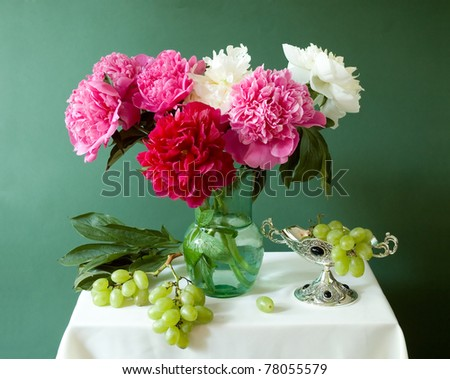 Huge bunch of red, white and pink peonies in vase with grapes on green