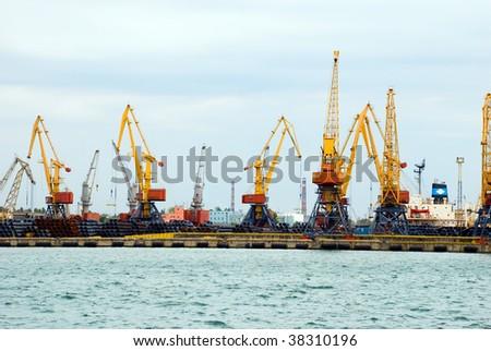 Huge cargo port cranes unload cargoes - stock photo