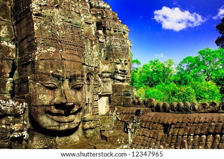 Huge carved face in ruins of temple in Cambodia - stock photo