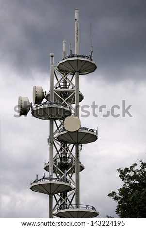 huge cell phone satellite tower against cloudy sky
