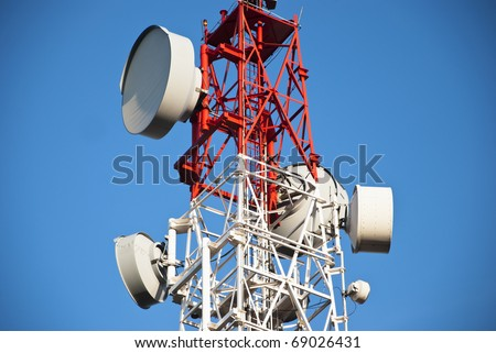 Huge communication antenna tower and satellite dishes against blue sky. - stock photo