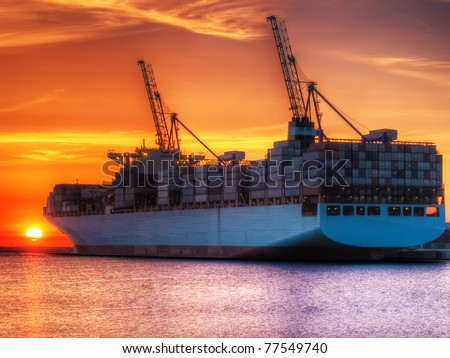 Huge container cargo ship at sunrise - stock photo